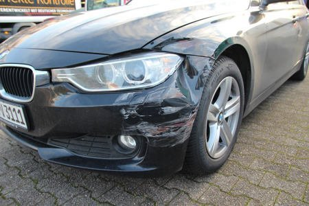 Foto eines beschädigten BMWs bei dem ein gutachten zur schadensaufnahme erstellt wird